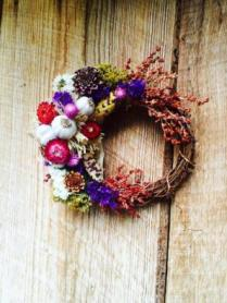 Grape vine wreath base with homegrown sorghum, Indian corn, garlic, statice, zinnias and strawflowers. Wild snakeweed accents.