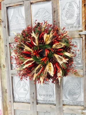 Christmas wreath with wild rosehip base, pinecones, chile pequin, Indian corn, wheat, and pine boughs.